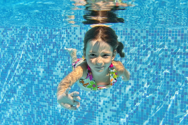 Happy smiling underwater child in swimming pool, beautiful girl swims and having fun. kids sport on family summer vacation. active holiday