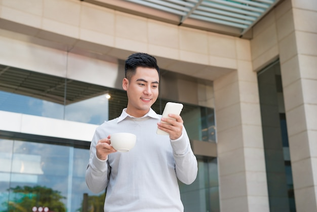 Happy smiling vietnamese business man outdoor with smartphone