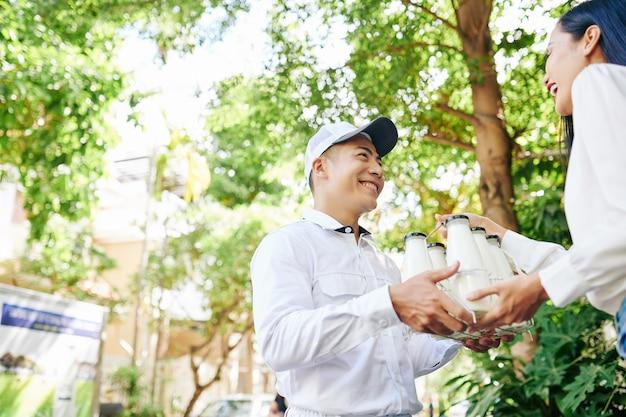 かなり若い女性に牛乳瓶のセットを与える幸せな笑顔のベトナムの配達人