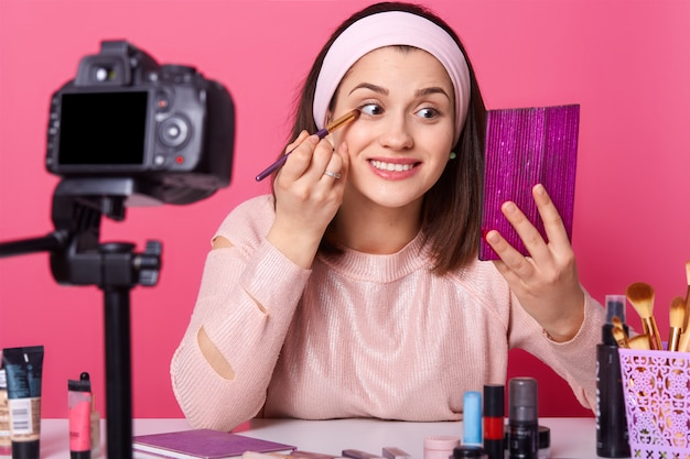 Happy smiling vlogger sits infront of camera and holds brush. young lady looks at mirror and applies eyeshadow