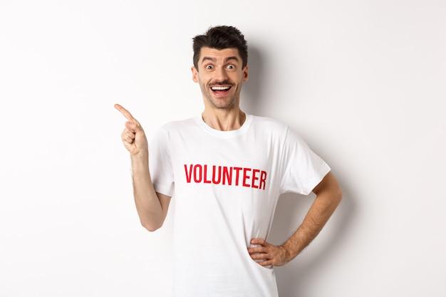 Счастливый улыбающийся доброволец, указывая пальцем влево на пространство для копирования, показывая объявление, белый.