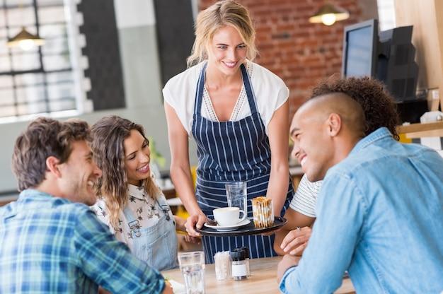 カフェテリアで友人の若い幸せなグループに食べ物を提供する幸せな笑顔のウェイトレス