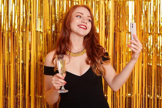 Sorridere felice con fare posa contro orpelli d'oro e fare selfie tramite un moderno smart phone, ragazza che indossa un abito nero, signora che tiene un bicchiere di vino, che celebra un evento importante.