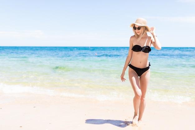 Donna sorridente felice in bikini e cappello da sole sulla ...