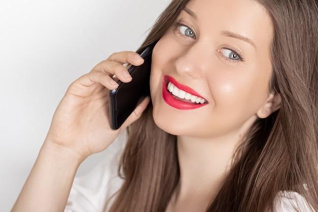 白い背景の人々の技術とコミュニケーションの概念のスマートフォンの肖像画を呼び出す幸せな笑顔の女性