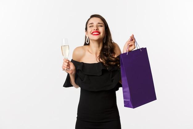 Donna sorridente felice che celebra, tenendo presente nella borsa della spesa e un bicchiere di champagne, in piedi in abito nero su sfondo bianco.
