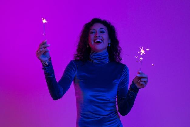 불꽃놀이와 함께 축 하 하는 행복 한 웃는 여자. 벵골 빛 신년 파티를 들고 소녀입니다.