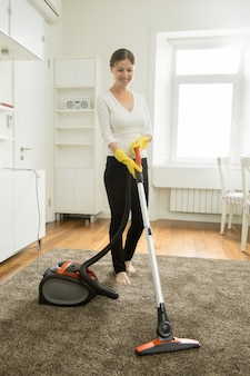 Happy smiling woman cleaning the carpet