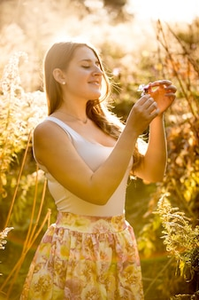 Happy smiling woman in dress looking at flower growing at field