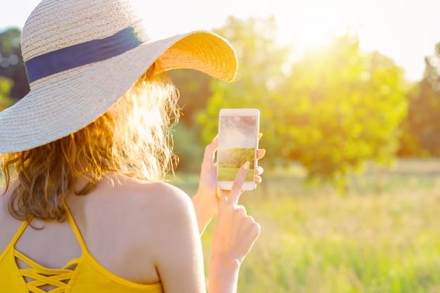 夏の帽子と明るい黄色の夏のドレスで幸せな笑顔の女性女性は、スマートフォン、緑豊かな公園の屋外で携帯電話で自然の写真写真を行います。夏、春のアクティブなアウトドアレジャーのコンセプト。