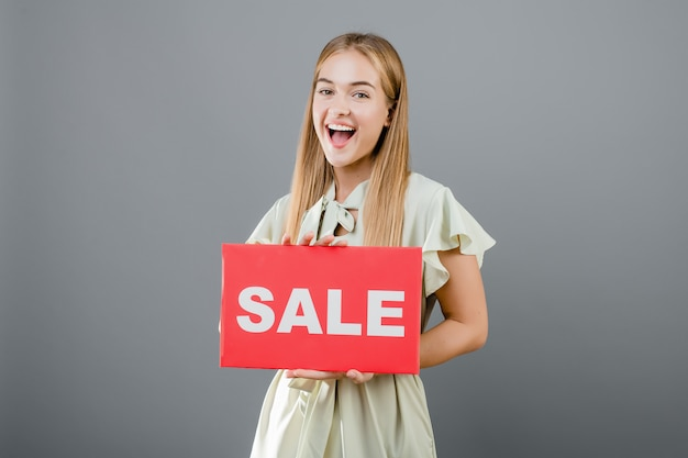 Happy smiling woman has sale sign isolated over grey
