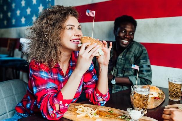 幸せな笑顔の女性は、カフェで男性と一緒にバーで休んで、話し、笑ってファーストフードを食べます。