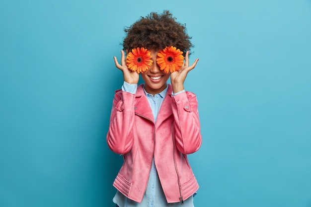 행복 한 웃는 여자 두 오렌지 gerberas로 얼굴을 숨기고 꽃을 좋아하며 행복과 기쁨을 표현합니다. 예쁜 꽃다발을 팔려고하는 쾌활한 꽃집, 꽃집에서 일