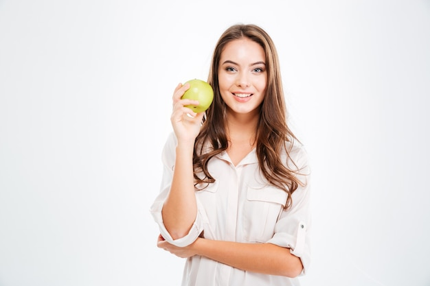 Happy smiling woman holding apple isolated on a white wall