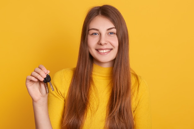 Happy smiling woman holding key in hands, wearing casual shirt, having long beautiful hair, buys new flat, looks happy, expressing positive emotions, being lucky.