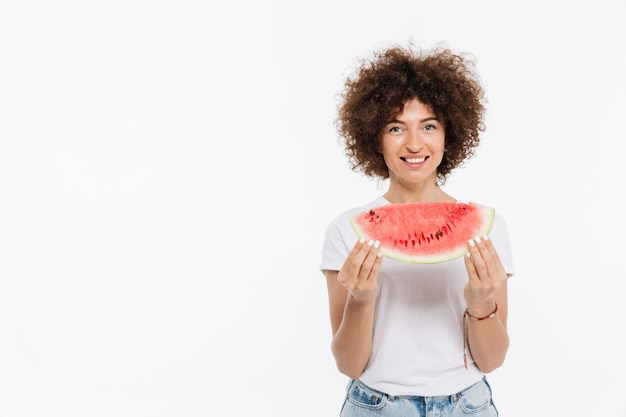 Happy smiling woman holding slice of a watermelon