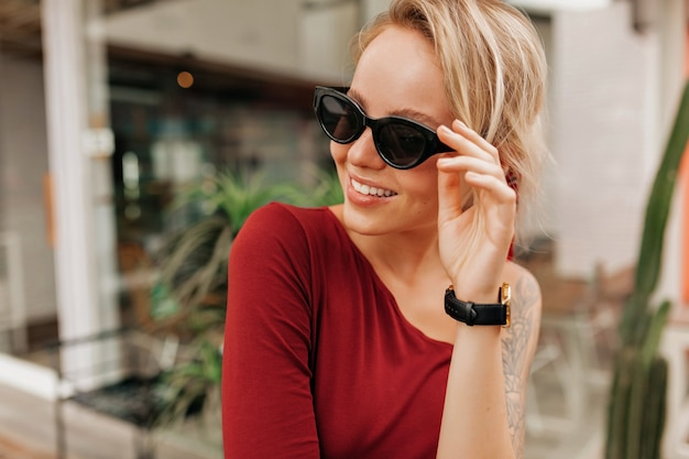 Счастливая улыбающаяся женщина, держащая солнцезащитные очки и смотрящая с улыбкой