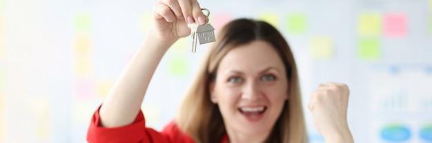 Счастливая улыбающаяся женщина, держащая ключи от квартиры, покупая концепцию собственного дома