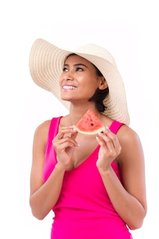 Happy, smiling woman holding watermelon, looking up at blank space