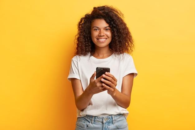 행복 한 웃는 여자는 휴대 전화, 휴대 전화에 문자 메시지를 보유하고, 인터넷을 서핑하고, 흰색 캐주얼 티셔츠와 청바지를 입은 곱슬 덥수룩 한 헤어 스타일을 가지고 있습니다.