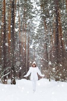 Счастливая улыбающаяся женщина в шубе ходит и смеется в зимнем лесу