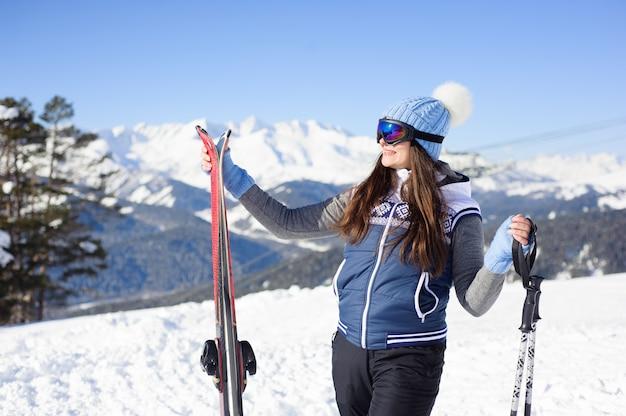 Счастливая усмехаясь женщина в изумлённых взглядах лыжи против подъема лыжи и чудесной предпосылки гор зимы.