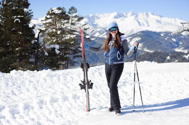 Счастливая улыбающаяся женщина в лыжных очках на фоне горнолыжного подъемника и прекрасных зимних гор.