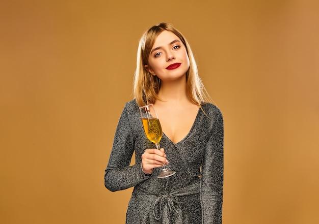 シャンパングラスとスタイリッシュな魅力的なドレスで幸せな笑顔の女性。