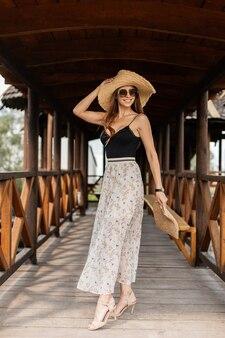 빈티지 밀짚 모자를 쓴 행복한 미소와 우아한 레이스 드레스를 입은 패션 짠 핸드백과 여름 신발이 해변 근처 나무 부두를 걷고 있다