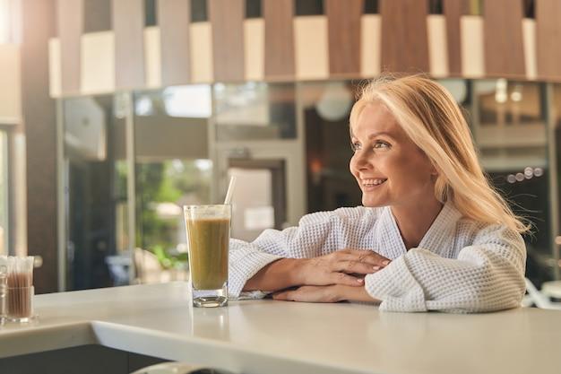 스파 리조트 호텔의 좋은 곳을 즐기는 흰색 부드러운 목욕 가운에 행복 웃는 여자