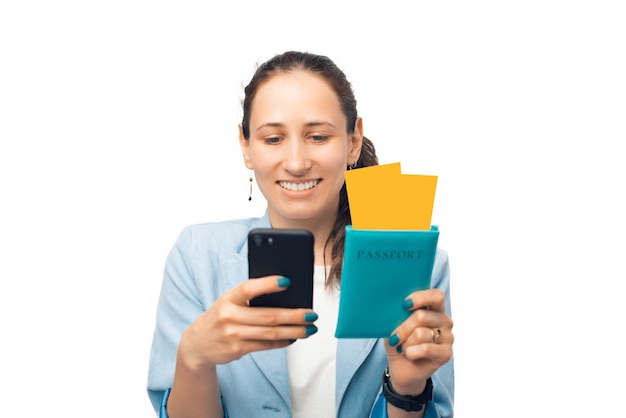행복한 미소를 짓고 있는 여성이 티켓이 있는 여권을 들고 전화로 비행 날짜를 확인하고 있습니다.