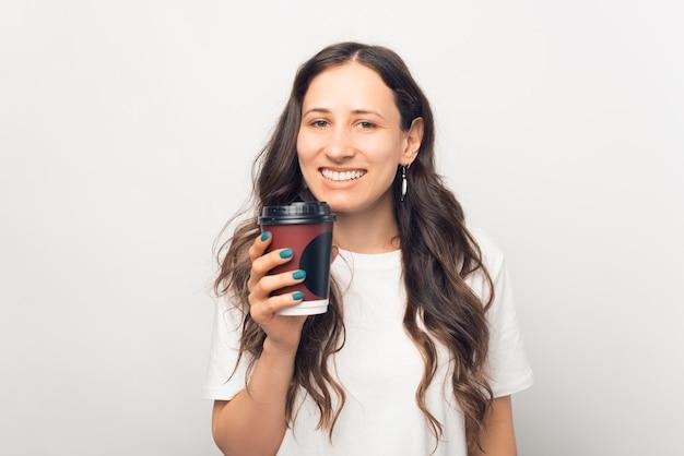 Счастливая улыбающаяся женщина держит бумажный стаканчик на вынос.