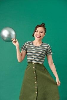 幸せな笑顔の女性は、緑の上で楽しんでいる空気の銀の風船を見ています。