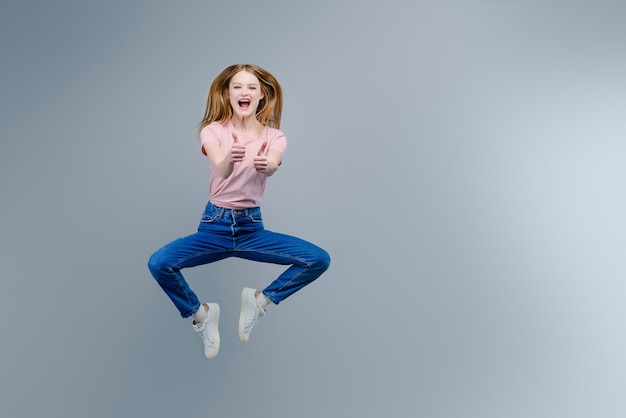 Happy smiling woman jumping with thumbs up isolated