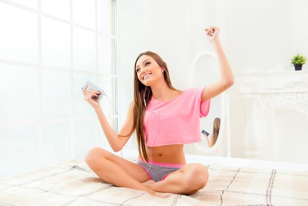 ベッドに座って音楽を聴いて踊る幸せな笑顔の女性