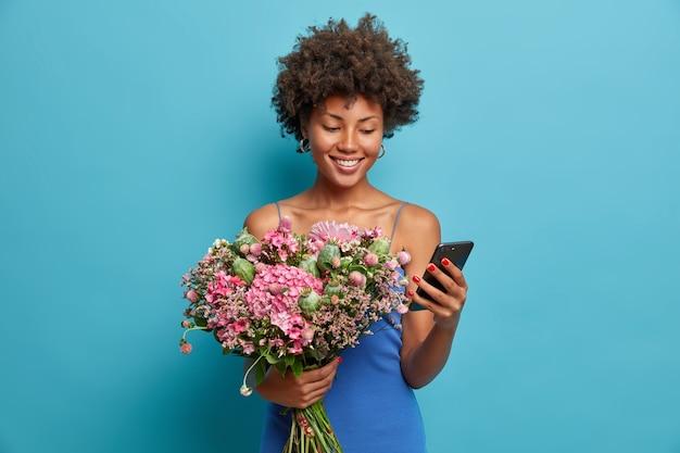La donna sorridente felice guarda il display dello smartphone sorride ampiamente, tiene il telefono cellulare e un mazzo di fiori