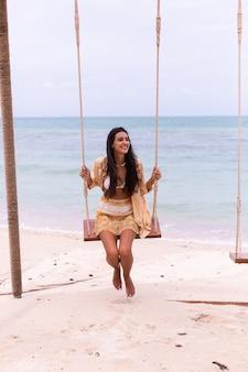 해변, 하루 따뜻한 빛에서 스윙에 행복 한 웃는 여자.