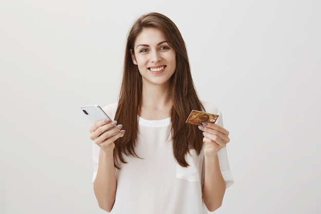 Happy smiling woman order online via smartphone app, holding credit card and mobile phone