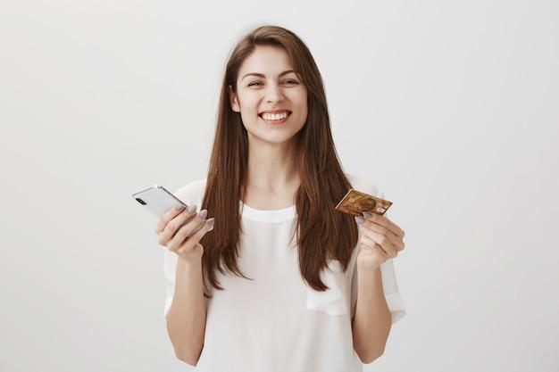 Donna sorridente felice ordina online tramite app per smartphone, tenendo la carta di credito e il telefono cellulare