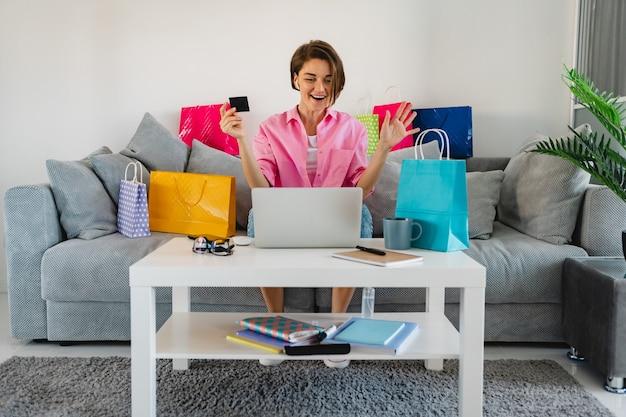 Donna sorridente felice in camicia rosa sul divano di casa tra i sacchetti della spesa colorati che tengono la carta di credito che paga in linea sul computer portatile
