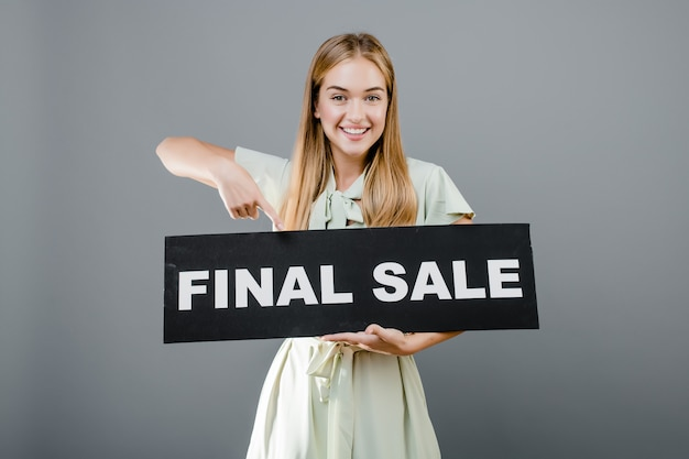 Happy smiling woman pointing finger at final sale sign isolated over grey