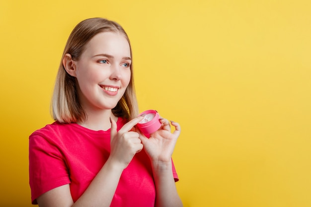 Happy smiling woman portrait applying moisturizing cream hand cream look side on copy space. teenager girl using skincare cosmetic product isolated over yellow color background.