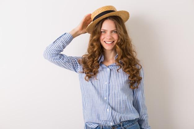 Donna sorridente felice che posa con il cappello di paglia su bianco
