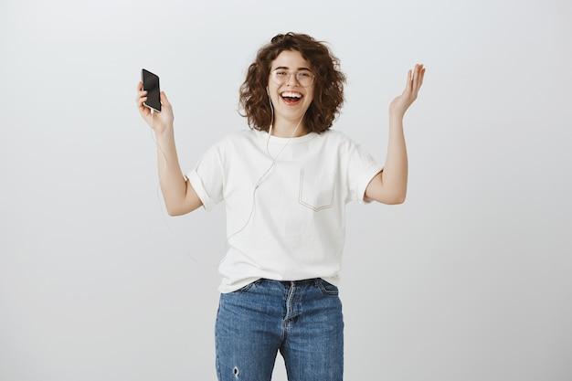 幸せな笑顔の女性が音楽のヘッドフォンを聴くとスマートフォンを保持していると喜んで手を上げる
