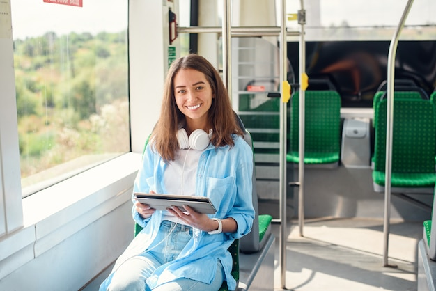 Happy smiling woman reads a tablet or ebook in a modern tram or subway. pretty girl rides for work in public transport.