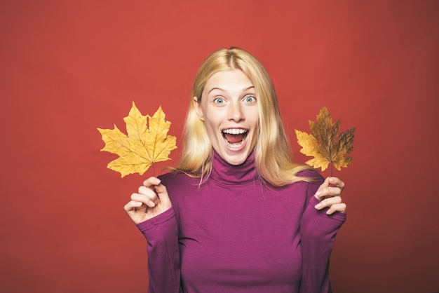 Happy smiling woman. sensual girl. model face. beauty face. fashion girls. autumn leaves isolated. autumn leaves background. autumn tree and autumn forest. red background.