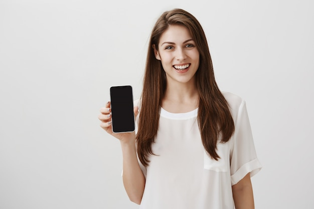 Happy smiling woman showing mobile screen, recommend app or shopping site