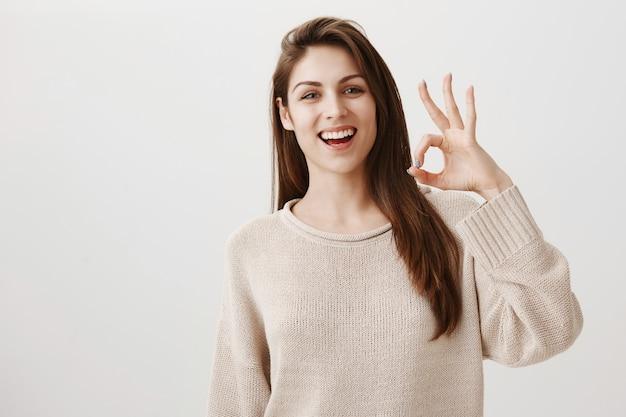 Donna sorridente felice che mostra il gesto giusto soddisfatto, approvare o raccomandare il prodotto