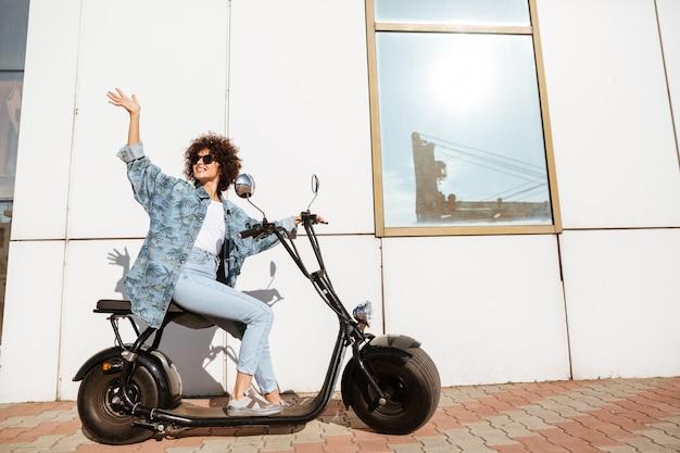 Donna sorridente felice che si siede su una motocicletta moderna