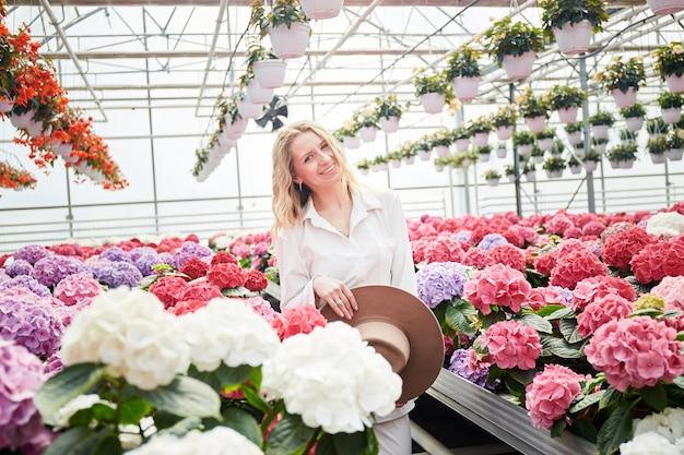 아름 다운 핑크 꽃 근처에 서 있는 행복 한 웃는 여자. 다채로운 수국과 산업 온실입니다. 온실에서 젊은 금발 여자. 주위에 화분에 꽃.